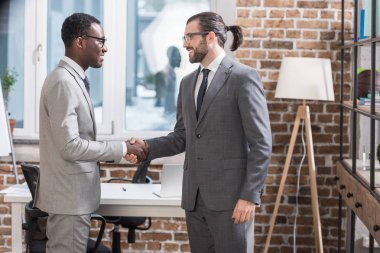 smiling multiethnic business partners shaking hands in modern office