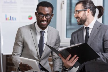 handsome businessman with folder and african american partner with digital tablet standing and smiling in office