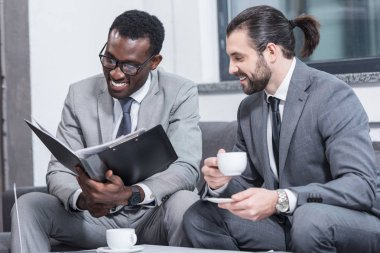 smiling multicultural business partners reading document and drinking coffee in office