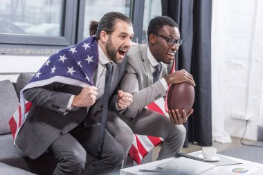 handsome multiethnic men in suits with american flag on shoulders watching american football match in office