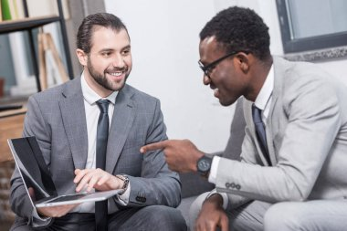 african american businessman pointing with finger at business partners laptop in office