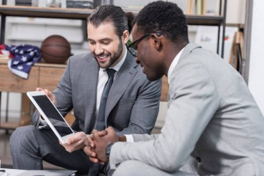 handsome businessman showing screen of digital tablet to african american business partner in office