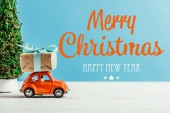 close-up shot of toy vehicle with gift box on blue background with merry christmas and happy new year lettering