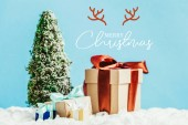 close-up shot of christmas gifts and miniature christmas tree standing on snow on blue background with merry christmas lettering with deer horns