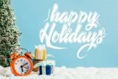 karácsonyi ajándékok, ébresztőóra és miniatűr karácsonyfa állt a hó kék háttér kellemes ünnepeket betűkkel közeli lövés