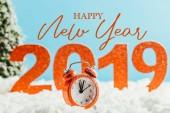 Fotografie velké červené 2019 čísla s retro budík stojící na sněhu na modrém podkladu s nápisem happy new year