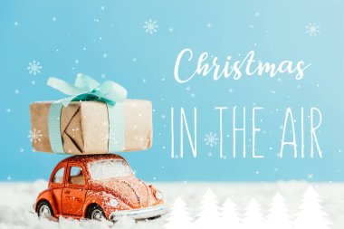 close-up shot of toy red car with christmas present riding by snow made of cotton on blue background with