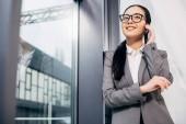 atraktivní podnikatelka stál u okna a mluví na smartphone