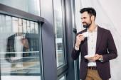 podnikatel, při pohledu na okna, usmíval se a drží šálek kávy v kanceláři
