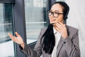 Photo pretty call center operator standing by window, touching headset and speaking in microphone in office