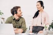 Fotografie s úsměvem call centrum operátor chtějí navzájem v úřadu