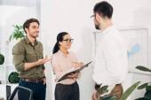 Happy úřad manažerů stojící před deska s uveřejněte, poznámky a mluví v úřadu
