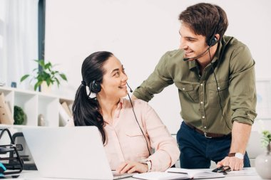 Call center operators smiling and looking to each other in office stock vector