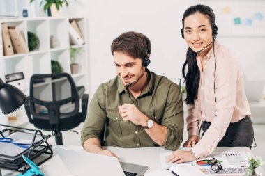 smiling call center operator working at laptop and pretty coworker looking at camera in office