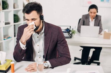 Sick call center operator with napkin blowing nose with coworker on background stock vector