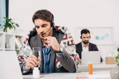 sick call center operator with blanket on shoulders holding glass of water and pill in office