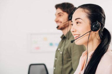 pretty call center operator smiling with handsome coworker on background in office