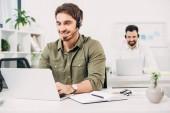 Szelektív összpontosít fejhallgató modern ügyfélszolgálaton dolgozó fiatal szolgáltató