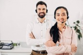 Fotografie Selective focus of female manager smiling with crossed arms while male coworker standing behind with headset