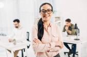 Usmívající se žena manažer stojí s překřížením rukou v úřadu