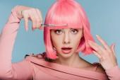 Šokovaný stylová holka stříhá růžové vlasy s nůžkami, samostatný na modré