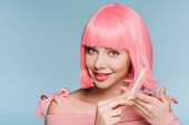 Fotografia smiling girl combing pink hair isolated on blue