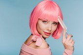 Fotografia attractive girl in pink wig posing with hair comb isolated on blue