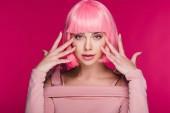 atraktivní stylová holka gestikuloval a pózuje v růžové paruce, izolované na růžové