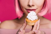 Photo cropped view of sensual girl holding sweet cupcake isolated on pink