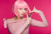 Fotografie attractive girl cutting pink hair with scissors isolated on pink