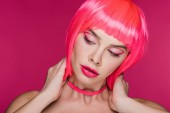 módní dívka pózuje v neonová růžová paruka, izolované na růžové