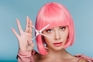 attractive fashionable girl in pink wig posing with scissors isolated on blue
