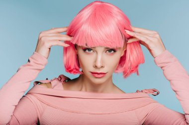 attractive stylish girl posing in pink wig isolated on blue