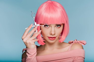 beautiful girl in pink wig posing with scissors isolated on blue
