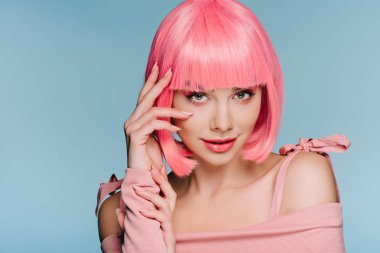 attractive fashionable girl posing in pink wig isolated on blue