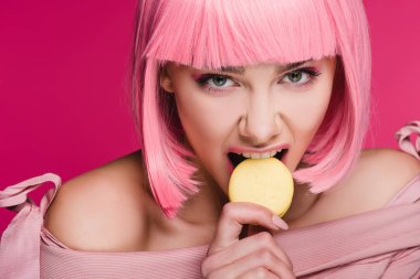 attractive aggressive girl in pink wig biting macaron isolated on pink