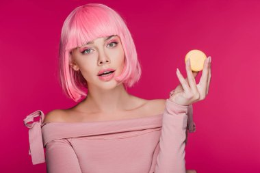 attractive fashionable girl in pink wig posing with yellow macaron isolated on pink