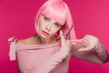 fashionable young woman cutting pink hair with scissors isolated on pink