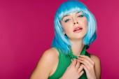 elegantní smyslná dívka pózuje v modrou parukou a zelený rolák, izolované na růžová