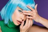 krásná dívka s modrý make-up a paruku ukazující nehty s manikúra, izolované na fialová