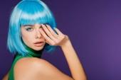 Fotografia attraente ragazza alla moda che propone in parrucca blu, isolata sulla porpora