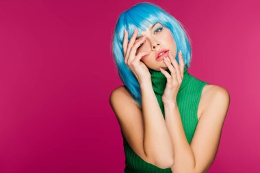 attractive girl with blue hair gesturing and posing isolated on pink