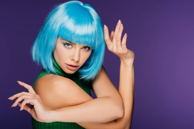 beautiful young woman posing in blue wig, isolated on purple