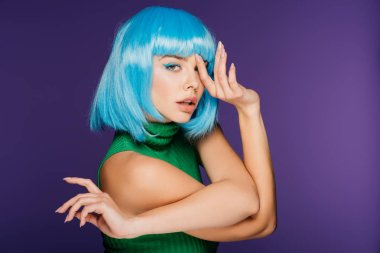 beautiful fashionable girl gesturing and posing in blue wig, isolated on purple