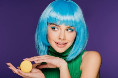 smiling young woman in blue wig posing with yellow macaron isolated on purple