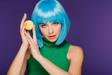 charming girl in blue wig posing with tasty macaron isolated on purple