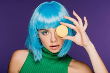 attractive sensual girl in blue wig posing with macaron isolated on purple