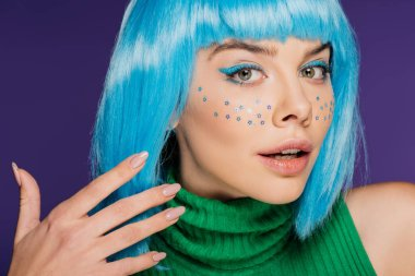 fashionable glamor woman with blue wig, makeup and stars on face, isolated on purple