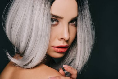 stylish young woman posing in grey wig, isolated on black