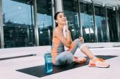 Fotografie lächelnde Asiatin sitzt auf Fitnessmatte und wischt sich im modernen Fitnessstudio mit Handtuch das Gesicht